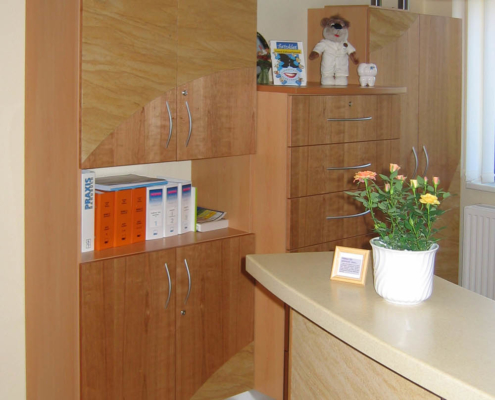 Schrank und Theke im Empfangsbereich einer Zahnarzpraxis in Leipzig, Sandstein- und Kirschbaum Furnier maroc design GmbH